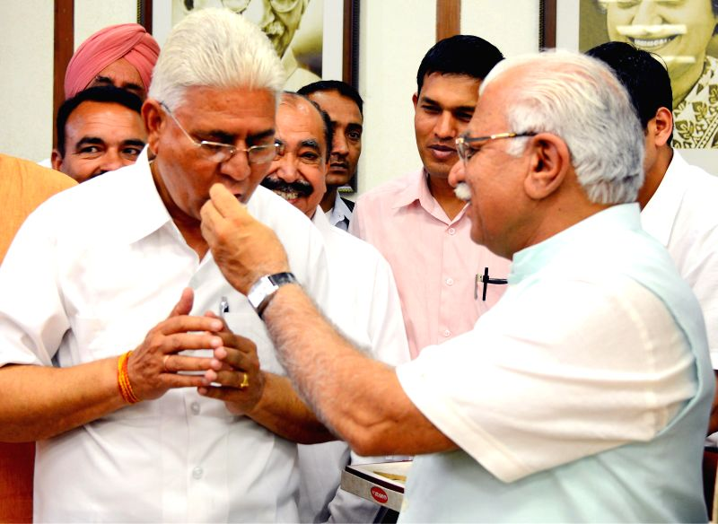 Haryana Chief Minister Manohar Lal Khattar administers with the newly appointed Chairman of Haryana Staff Selection Commission (HSSC) Bharat Bhushan in Chandigarh, on March 25, 2015. - Manohar Lal Khattar