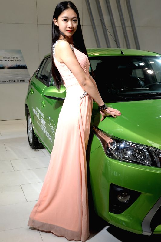 A model presents a car during the 2014 Changchun spring automotive exhibition in Changchun, capital of northeast China's Jilin Province, April 25, 2014. The auto