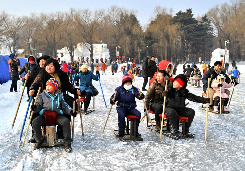 Children and their parents enjoy sledding at Nanhu Park in Changchun, capital of northeast China's Jilin Province, Jan. 11, 2015.