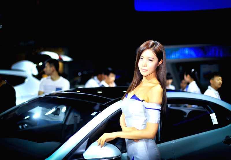 A model presents a car at the 11th China Changchun International Automobile Expo in Changchun, capital of northeast China's Jilin Province, July 11, 2014. The ...