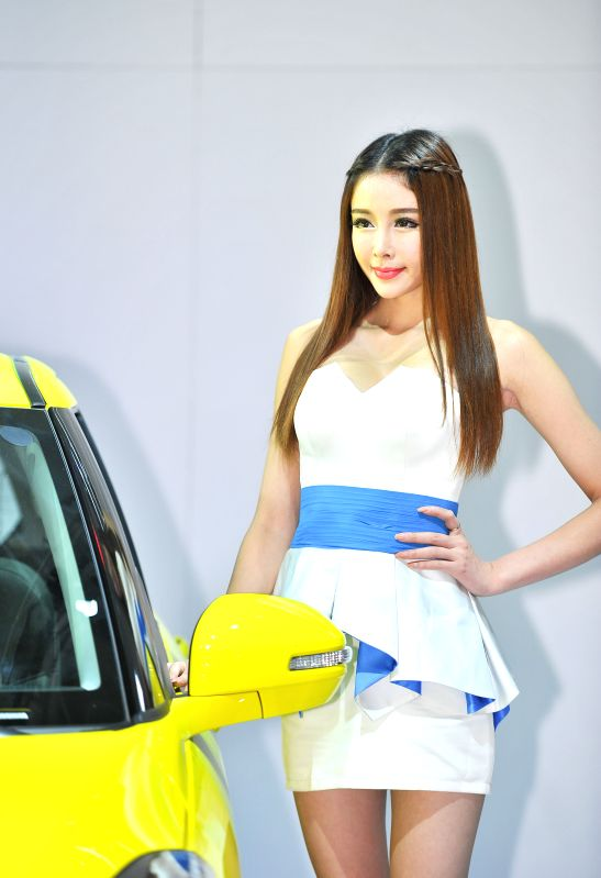 A model presents a car at the 11th China Changchun International Automobile Expo in Changchun, capital of northeast China's Jilin Province, July 12, 2014. The ...