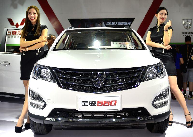CHANGCHUN, July 15, 2016 - Models display a Baojun 560 at the 13th China Changchun International Automobile Expo held in Changchun, northeast China's Jilin Province, July 15, 2016. More than 1300 ...