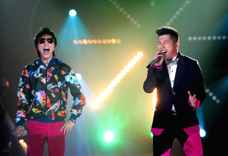 """Singer Chen Yufan (L) and Hu Haiquan perform in the biennial concert of """"I'm a singer"""", a reality music show for professional singers, in Changsha, ..."""