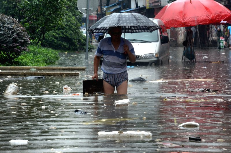 A citizen walks on a flooded road in Changsha City, capital of central China's Hunan Province, July 15, 2014. A rainstorm hit the city on Tuesday and the local ...