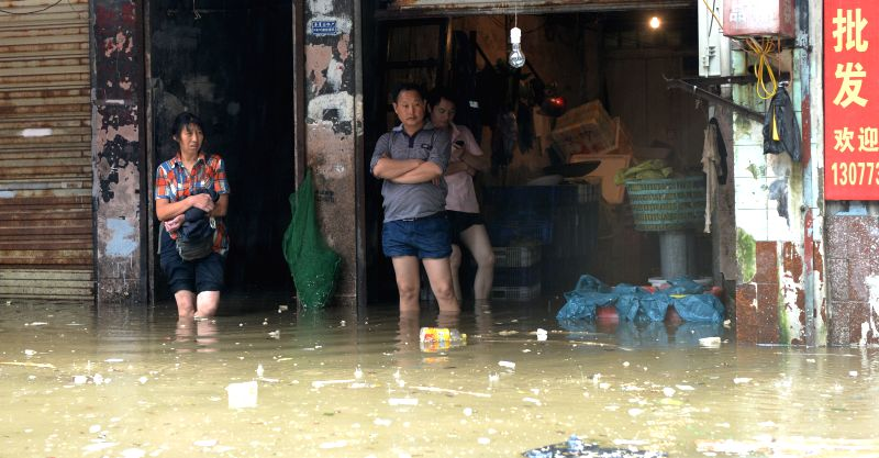 Residents watch the rainstorm helplessly as they stand on a flooded road in Changsha City, capital of central China's Hunan Province, July 15, 2014. A rainstorm ...