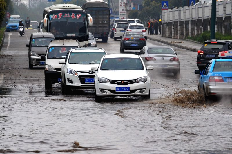 Cars run on a waterlogged road in Changsha, capital of central China's Hunan Province, March 23, 2015. Due to heavy rain, many areas in Changsha suffered ...