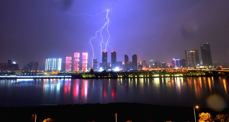 Lightning hits the sky above the urban areas along the Xiangjiang River in Changsha, capital of central China's Hunan Province, March 22, 2015. (Xinhua/Long ...