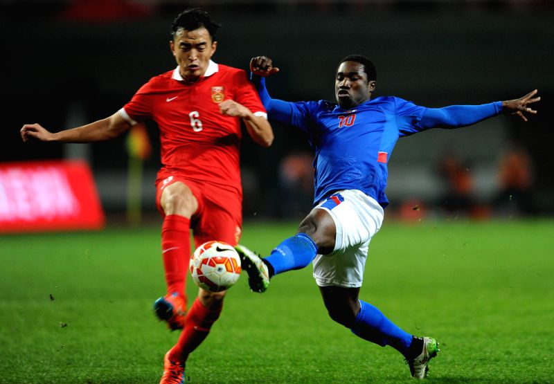 China's Feng Xiaoting (L) vies with Haiti's Jeff Louis during their soccer friendly match at the Changsha Helong Sport Center in Changsha, capital of central ...