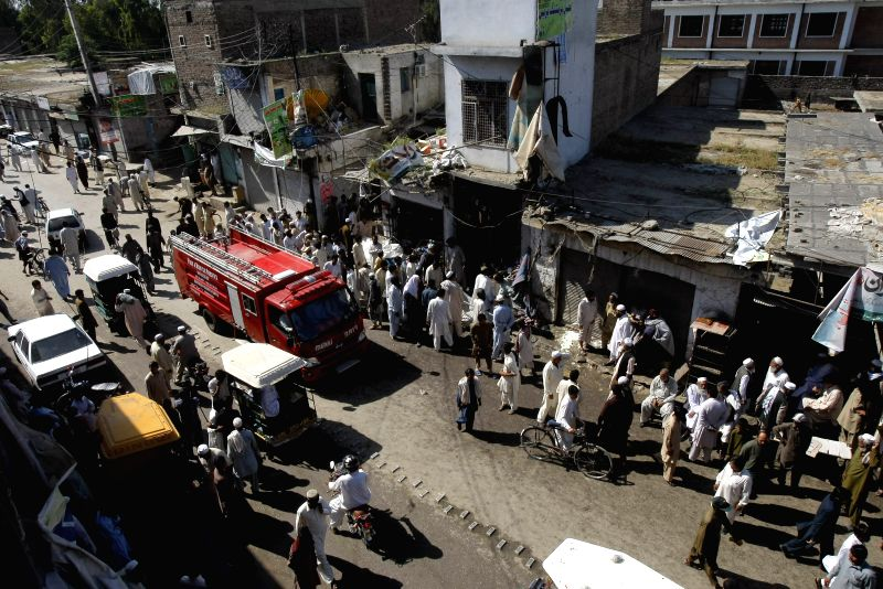 People gather at the site of a blast in northwest Pakistan's Charsadda, on April 22, 2014. At least four people were killed and 33 others injured when a bomb ...