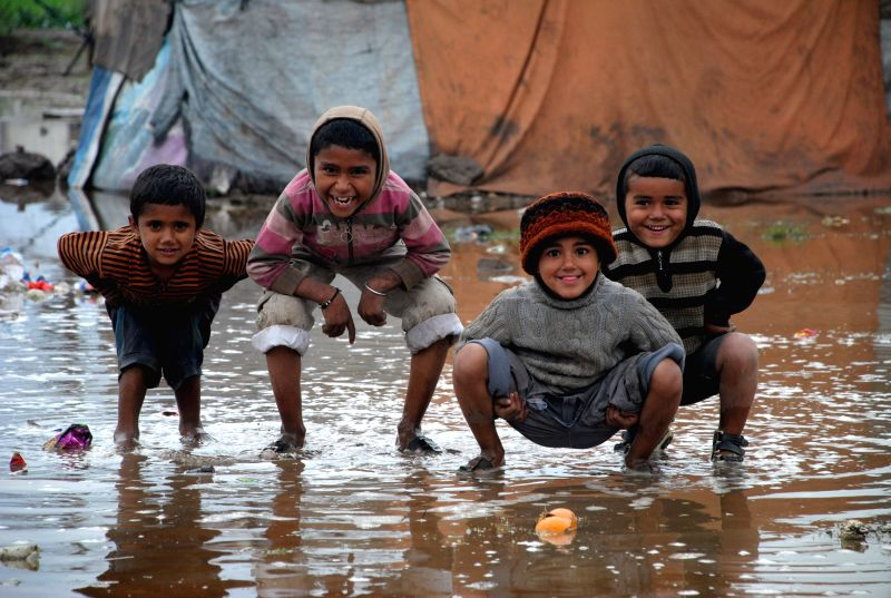 Pakistani boys play in rain water in northwest Pakistan's Charsadda on March 3, 2015. At least 10 people including three children were killed and several others ...