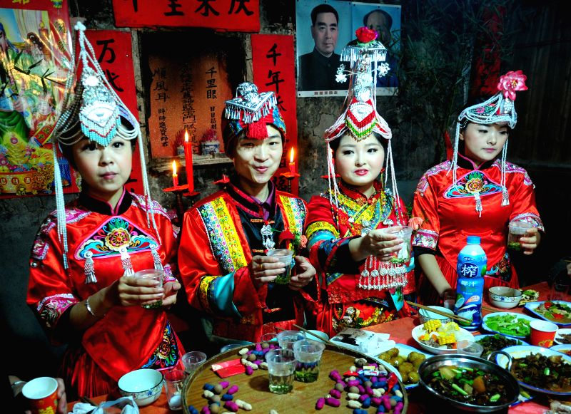 Chen Jianjie (2nd L) and Lan Yunli (2nd R), a young couple of She ethnic group, propose a toast to guests at their wedding ceremony in Baimaxia Village of Wuyi ...