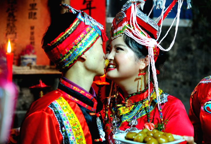 Chen Jianjie (L) and Lan Yunli, a young couple of She ethnic group, eats Tangyuan, a Chinese sweet dumpling, at their wedding ceremony in Baimaxia Village of Wuyi ...