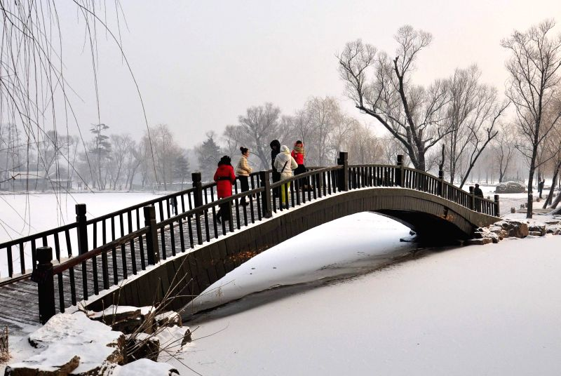 Chengde (China): People tour around the Summer Resort in Chengde, north China's Hebei Province, Dec. 10, 2014. Chengde witnessed the first snowfall this year on Wednesday.