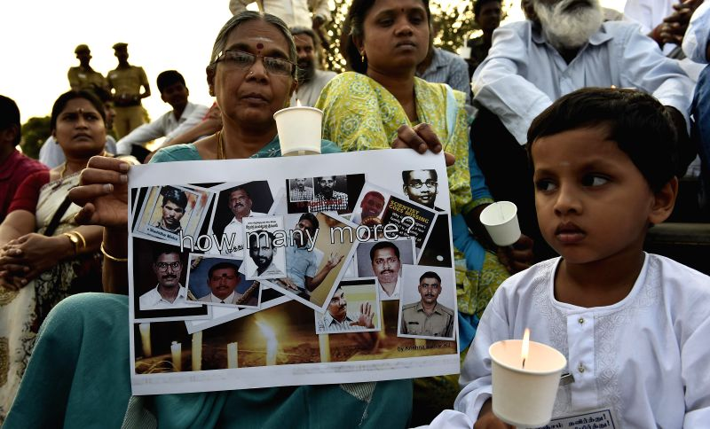 A child  participates in a candlelight vigil to condemn the mysterious death of Bangalore Additional Commissioner of Commercial Taxes D K Ravi, at Marina beach in Chennai on March 21, 2015.