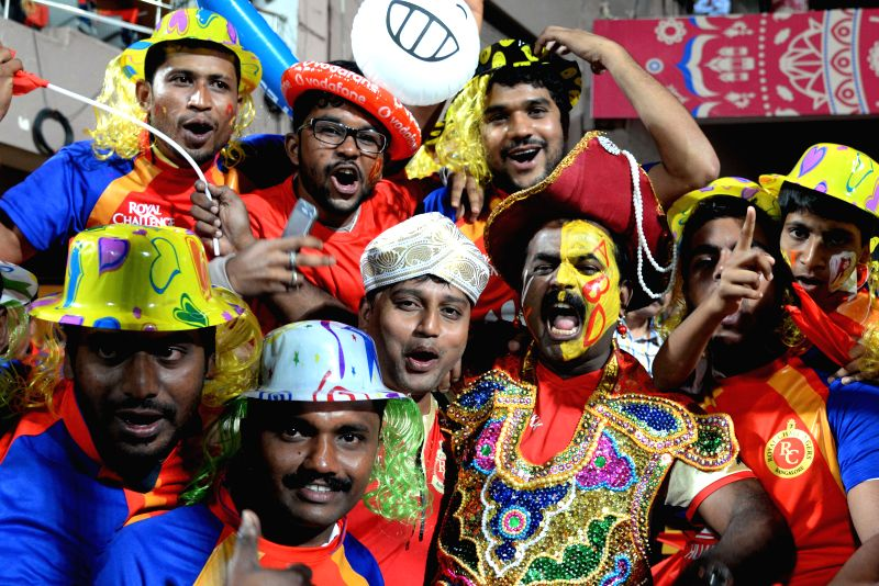 Cricket fans cheer during an IPL-2015 match between Royal Challengers Bangalore and Sunrisers Hyderabad at M Chinnaswamy Stadium, in Bengaluru, on April 13, 2015.
