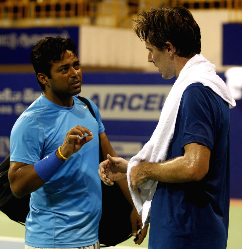 Indian Tennis player Leander Paes interacts with France`s Tennis player Edouard Roger-Vasselin during a practice session of ATP Chennai Open 2015 at SDAT Tennis Stadium in Chennai on Jan. 3,