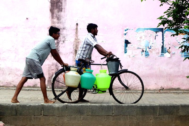 Chennai: Men carry water on a bicycle after collecting it from street-side taps amid the ongoing water crisis in Chennai, on July 2, 2019. (Photo: IANS)
