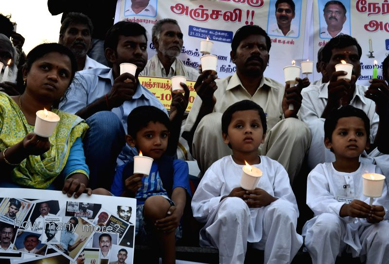 People participate in a candlelight vigil to condemn the mysterious death of Bangalore Additional Commissioner of Commercial Taxes D K Ravi, at Marina beach in Chennai on March 21, 2015.
