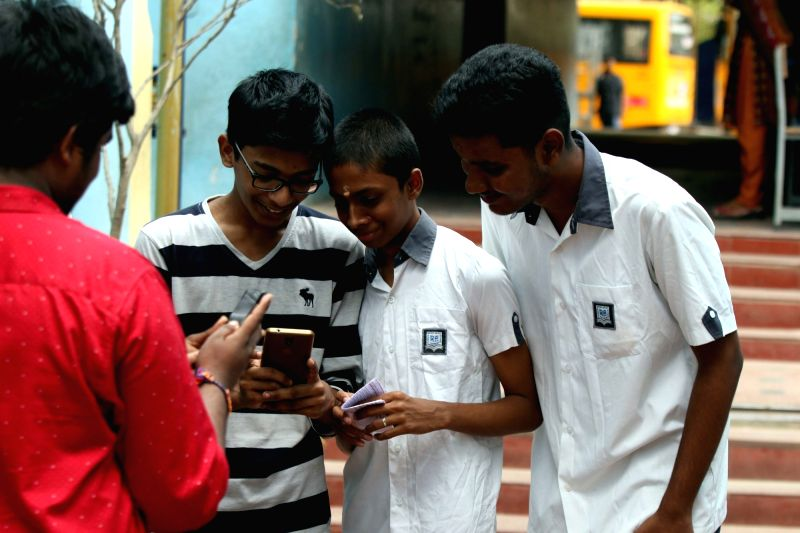 Chennai: Students check their results to Tamil Nadu Higher Secondary Certificate (HSC) Class XII examinations on their mobile phones, in Chennai on May 16, 2018.