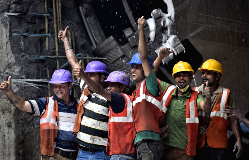 Workers celebrating in front of the tunnel boring machine which broke the last piece of the wall at Thirumangalam station to mark the completion of the tunnel mining between Thirumangalam ...