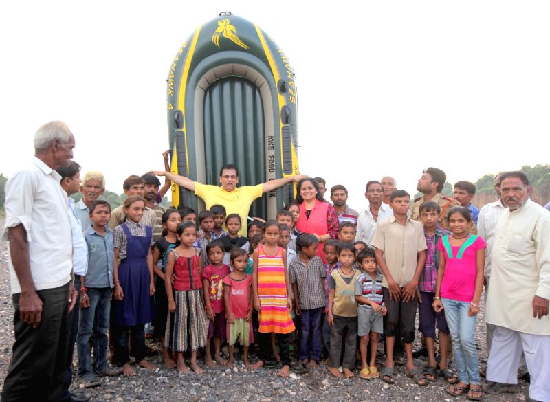 Chhota Udaipur: New York-based Indian-American couple Ratna and Varinder Bhalla with the children of Gujarat's Chhota Udaipur district who once had to swim across the raging Hiran river every day ...