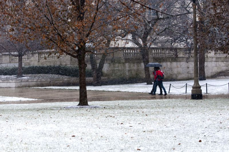 Local residents walk in snow in Chicago downtown, the United States, on Nov. 24, 2014. About 400 flights were delayed at O'Hare International airport and almost 120 were canceled, local ...