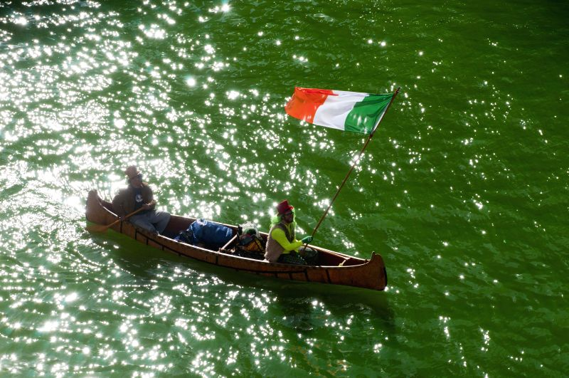 Two people sit in a boat in the green-dyed Chicago River ahead of the St. Patrick's Day parade in Chicago, the Untied States on  March 14, 2015. The celebration of ...