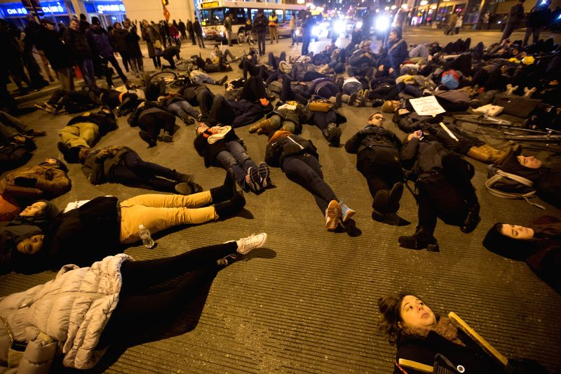 Protesters lie on a street of Chicago, the United States, on night of Dec. 4, 2014, to demonstrate concerns over the chokehold death of a black man caused by a white police officer of the ...