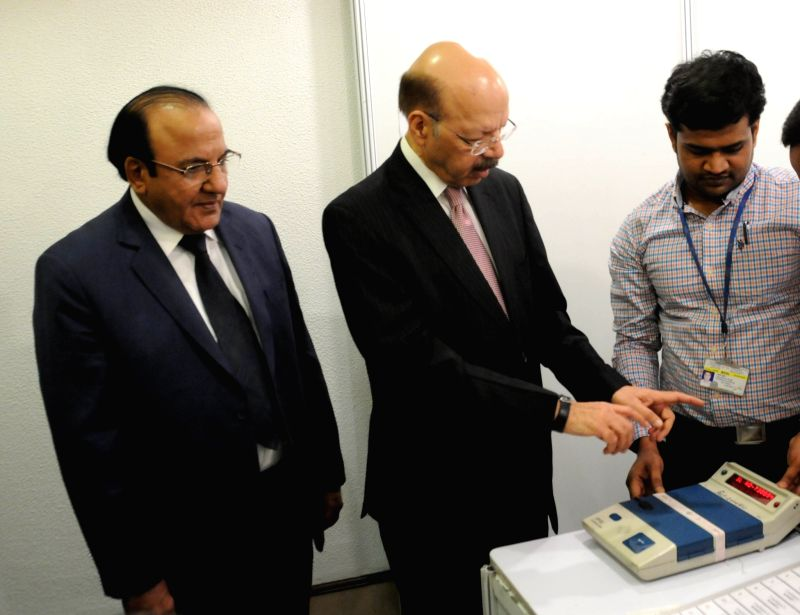 """Chief Election Commissioner Nasim Zaidi inspects the Electronic Voting Machines and Voter-verifiable paper audit trail (VVPAT) during a press conference on """"EVM Challenge"""" called ..."""