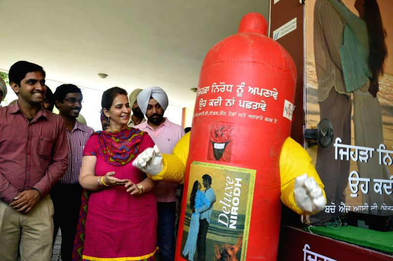 Chief Parliamentary Secretary (Health) Navjot Kaur Sidhu with a `Condom Man` before launching an AIDS Awareness Program in Amritsar on July 10, 2014. - Navjot Kaur Sidhu