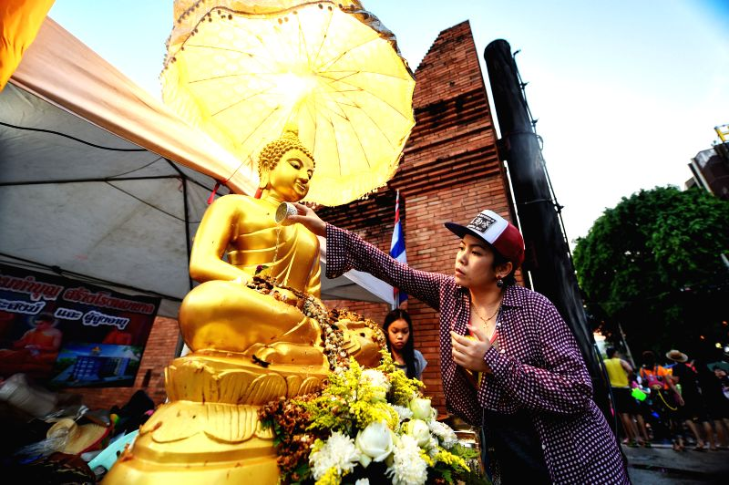 A woman cleans up a statue of Buddha during celebrations for Songkran Festival, Thailand's traditional New Year Festival, in Chieng Mai, Thailand, April 13, ...