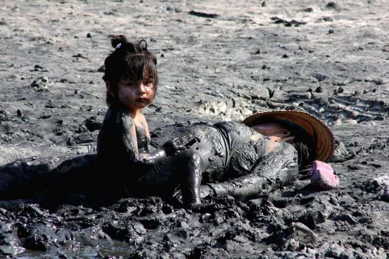 "A girl and her mother are seen smeared with mud from the ""medicinal lagoon La Milagrosa"", in the Chilca district, Canete province, Lima department, Peru, .."