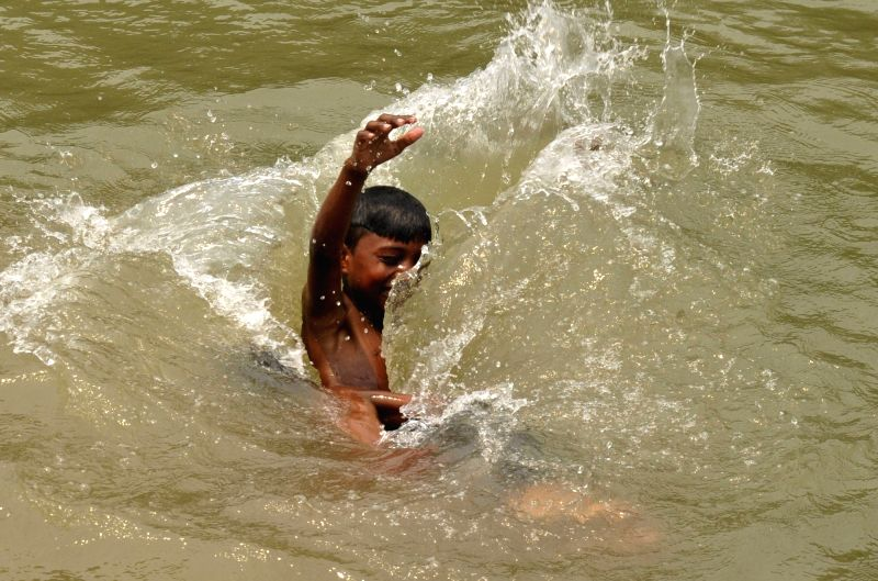 Children beat the heat in a pond in Amritsar on May 9, 2017.