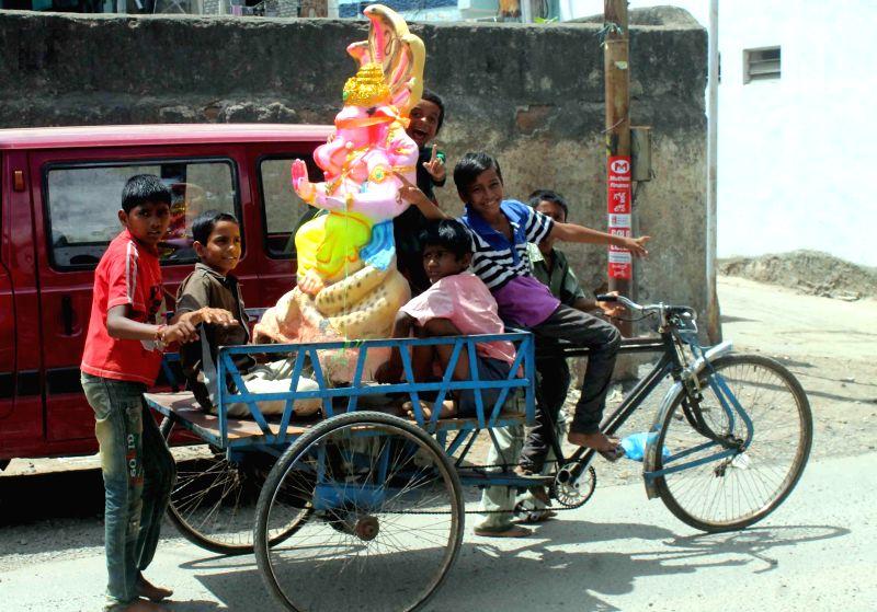 Children carry a Ganesh Idol ahead of Ganesh Chaturthi, in Hyderabad on Aug 24, 2014.