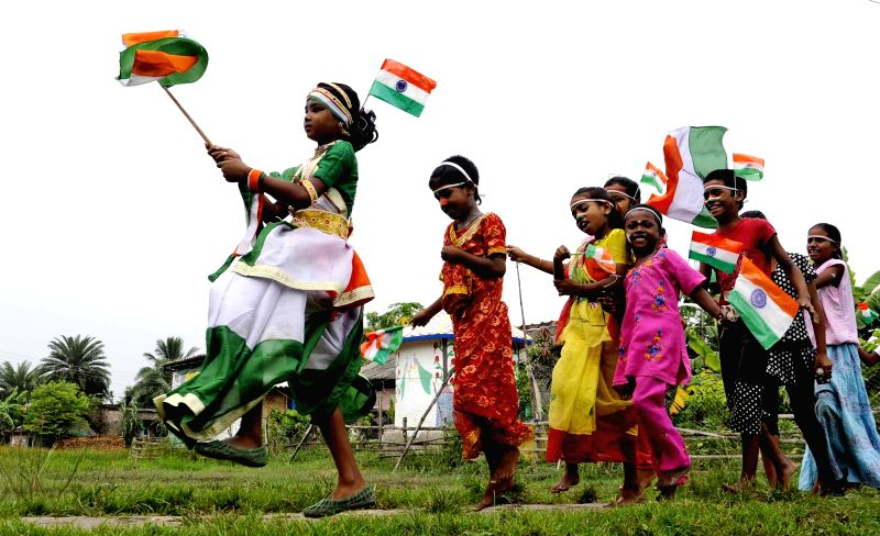 Children celebrate on the eve of Independence Day at Subhashgram in West Bengal's South 24 Parganas on Aug 14, 2014.