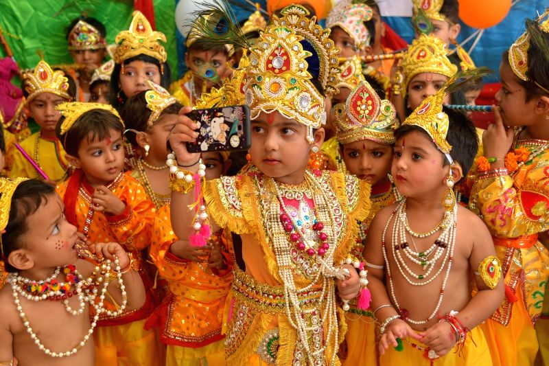 Children dressed up as Lord Krishna pose for a selfie during Janmashtami celebrations