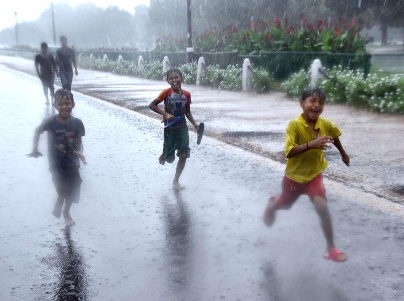 Children enjoy rains at India Gate, in New Delhi, on Aug 10, 2018.