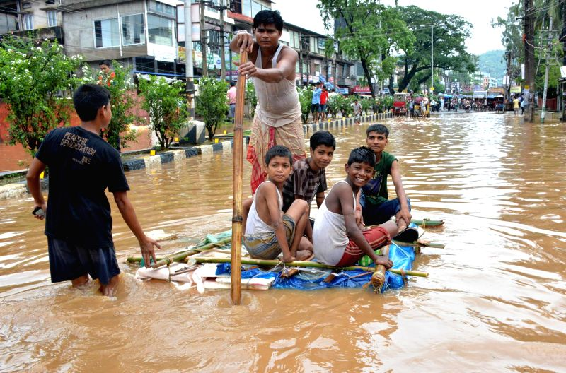 Children enjoy themselves aboard a raft on waterlogged Zoo road after heavy showers in Guwahati on June 27, 2014.