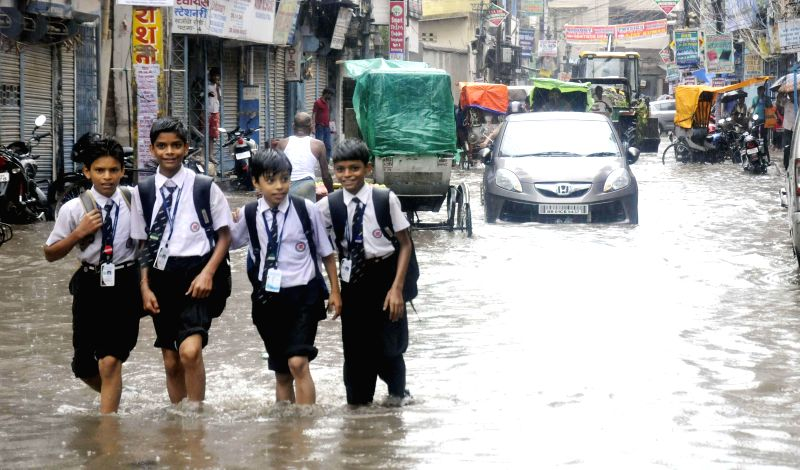 Children enjoy themselves as they wade through waterlogged streets of Patna on Aug 13, 2014.