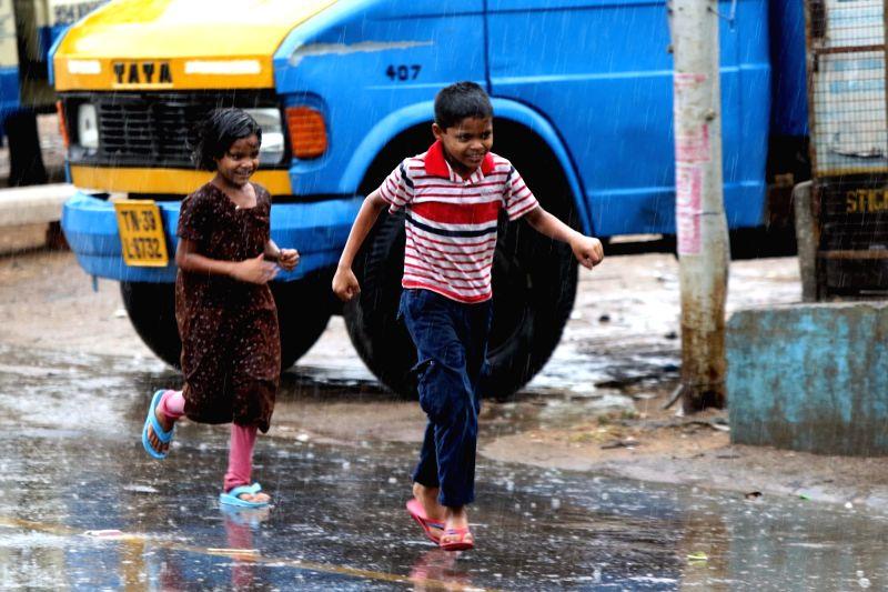 Children enjoy themselves during rains, in Chennai on June 6, 2018.