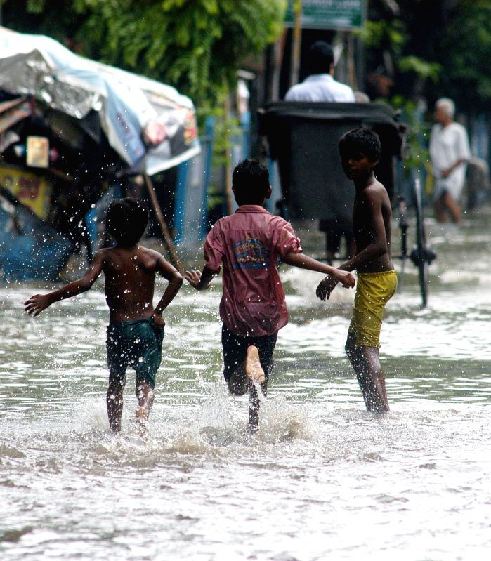 Children enjoy themselves in waterlogged roads of Kolkata after rains on July 1, 2014.