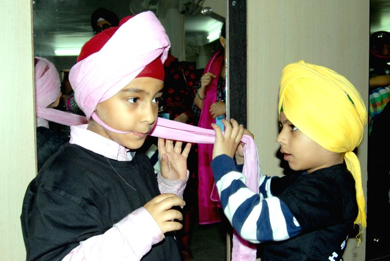 Children helping each other in a Turban Competition organised during the inaugural day of the three day long Sikh Summit at the Singh Sabha Gurduwara in Shillong on April 18, 2014.