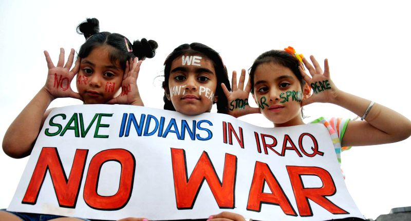 Children hold a placard reading 'Save Indians in Iraq - No War' in Amritsar on June 22, 2014.