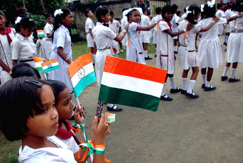 Children hold national flags as they celebrate Independence Day in Kolkata on Aug 15, 2014.