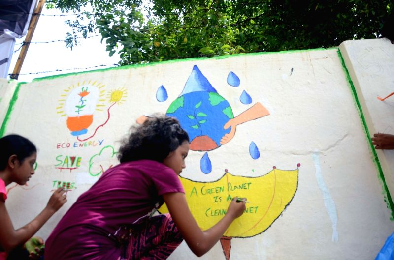 Children paint on walls on World Environment Day in Mumbai on June 5, 2017.
