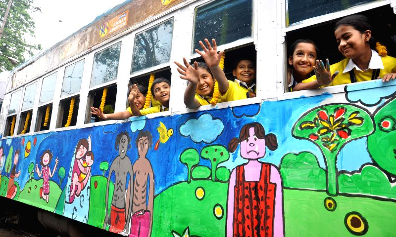 Children painting on a tram during a program on `Art for Nutrition` in Kolkata on July 24, 2014.