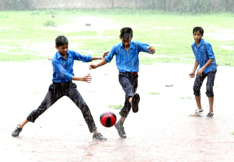 Children play football during rains, in Mathura on July 25, 2018.