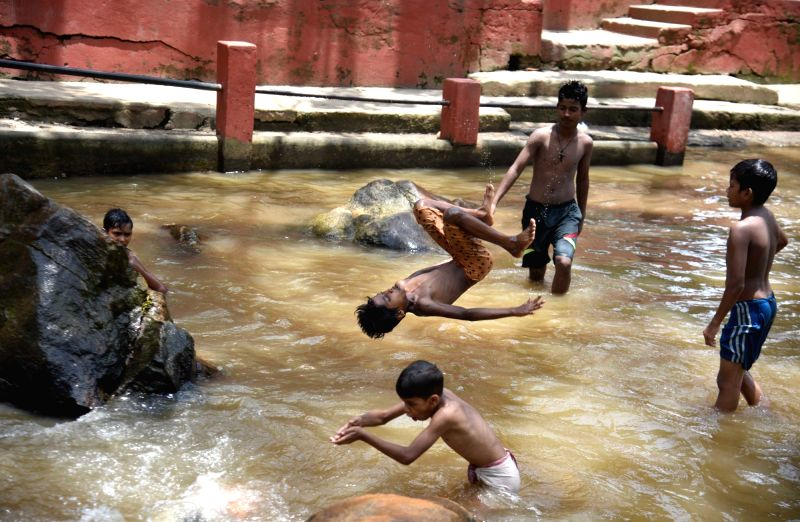 Children play in Basistha river on a hot day, in Guwahati, on July 20, 2018.