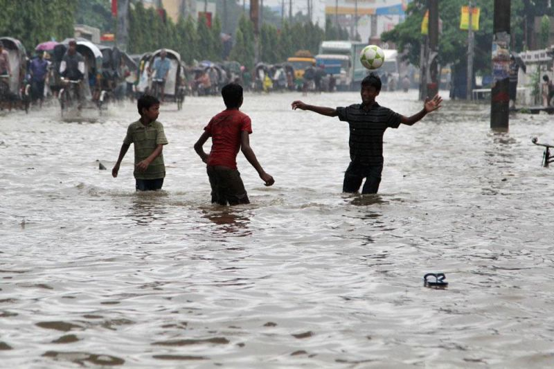 Children play with a football on water logged streets of Chittagong's Muradpur in Bangladesh on June 20, 2014.