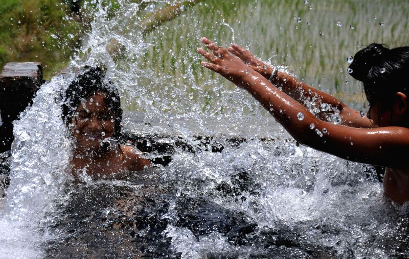 Children play with water during summers in Amritsar on July 8, 2014.